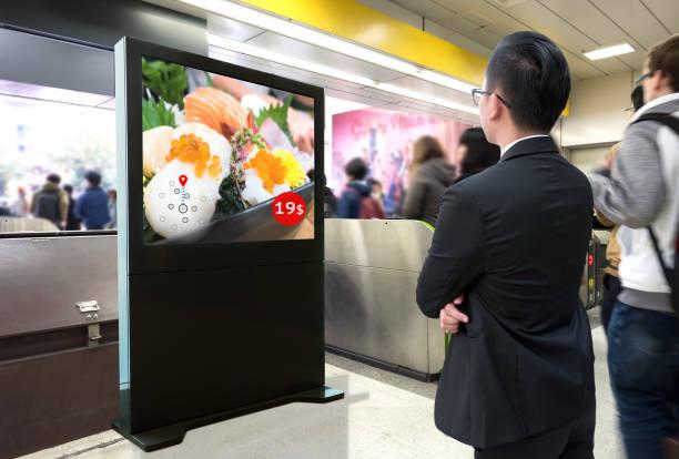 Inteligente Digital Signage, marketing de realidad aumentada y concepto de reconocimiento de rostro. Inteligencia artificial interactivo digital anuncio sushi restaurante japonés en tren metro o en el cielo. - foto de stock