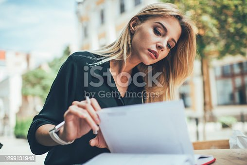 Intelligent female student 20s checking information notes in education textbook during learning in sidewalk cafe, beautiful Caucasian woman keep personal diary using notepad on leisure outdoors
