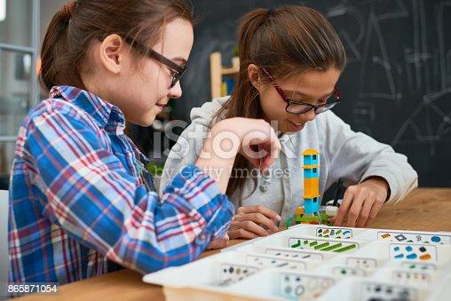 865870702 istock photo Intelligent girls making tower from building blocks 865871054