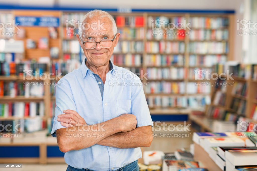 Intelligent positive older man standing in library on background with...