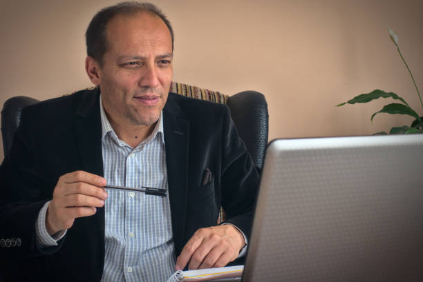 Intelligent professional senior man working from home with laptop holds a pen stock photo