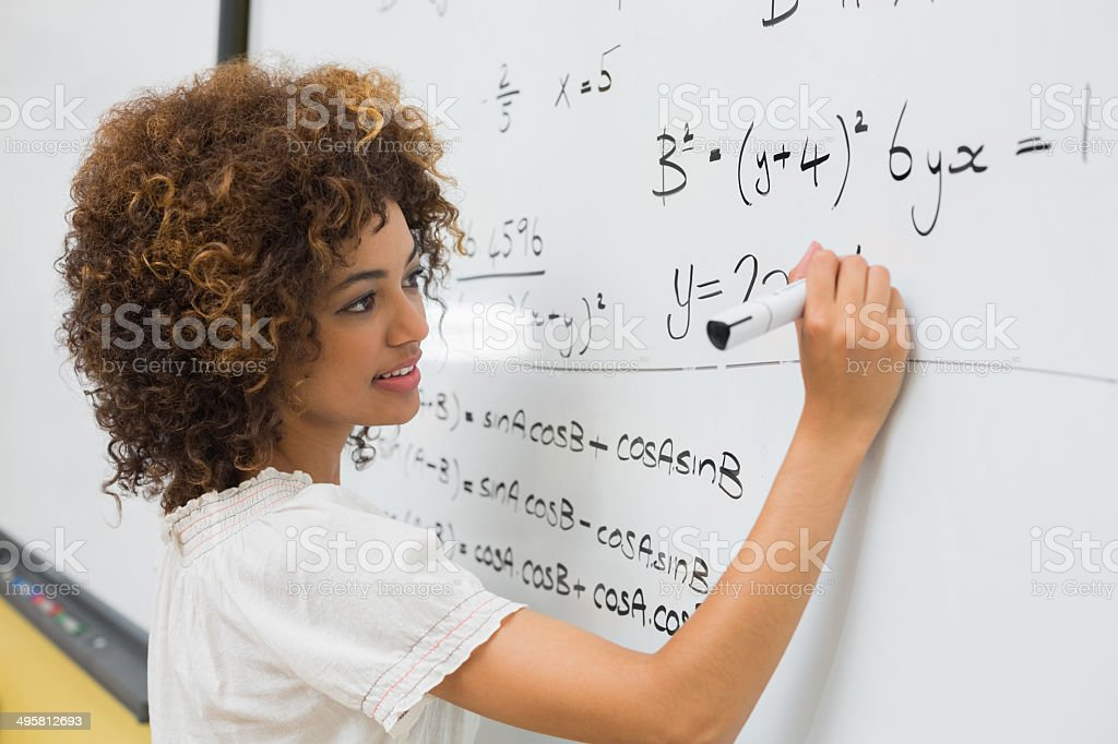 Intelligent student solving a math problem on whiteboard stock photo