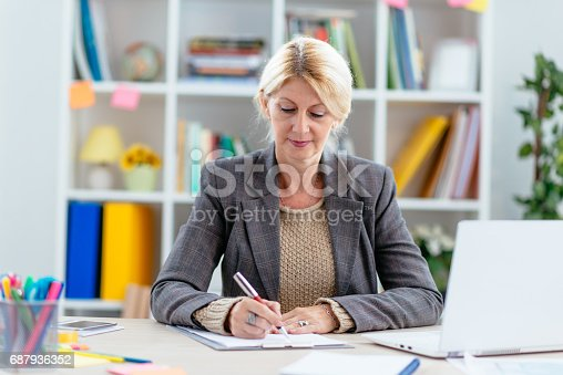 istock Intelligent woman in office, signing relevant documents 687936352