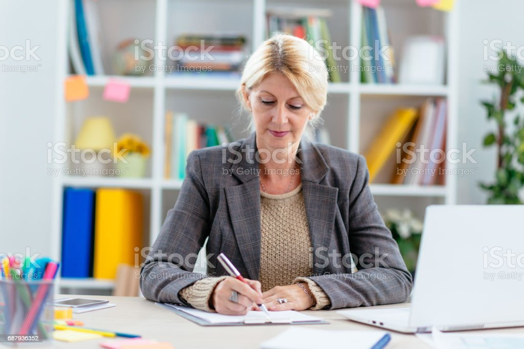 Intelligent woman in office, signing relevant documents stock photo
