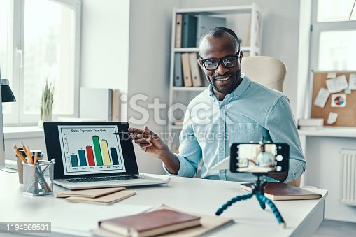 Intelligent young African man in shirt showing chart and telling something while making social media video