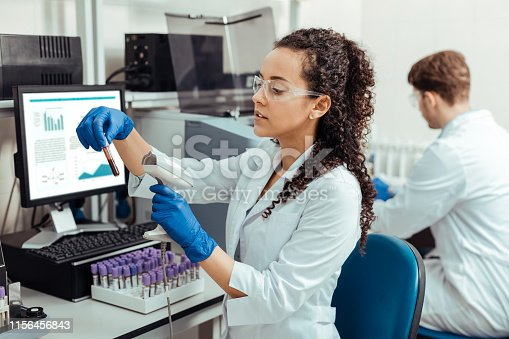 Blood parameters. Intelligent young woman scanning the test tube while checking blood parameters