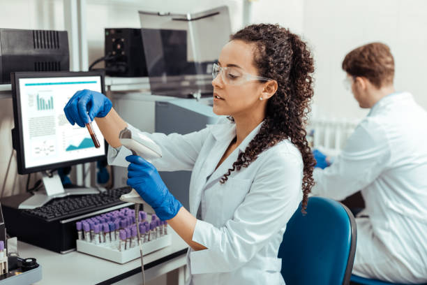 Intelligent young woman scanning the test tube stock photo