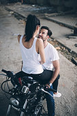 Love couple sitting on a bike in an old ruined garage.