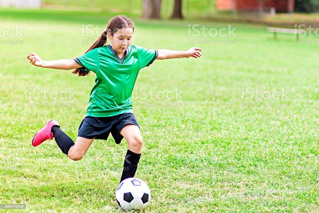 Intense Hispanic Preteen Girl Kicks Soccer Ball Stock
