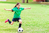 Focused Hispanic girl prepares to kick soccer ball. Her arms are outstetched as she pulls her foot back to prepare to kick the ball. The has long brown hair in a ponytail. She is wearing a green jersey, black shorts, black socks and pink cleats. She is the only player seen in the photo.
