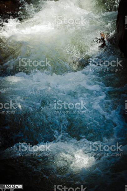 Photo of Intense light reflex on fast flow of clean and fresh mountain river.