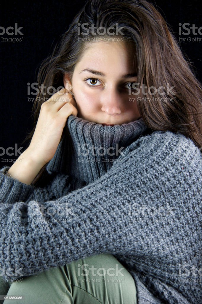 intense look of a beautiful brunette covering part of her face  with a turtleneck sweater royalty-free stock photo