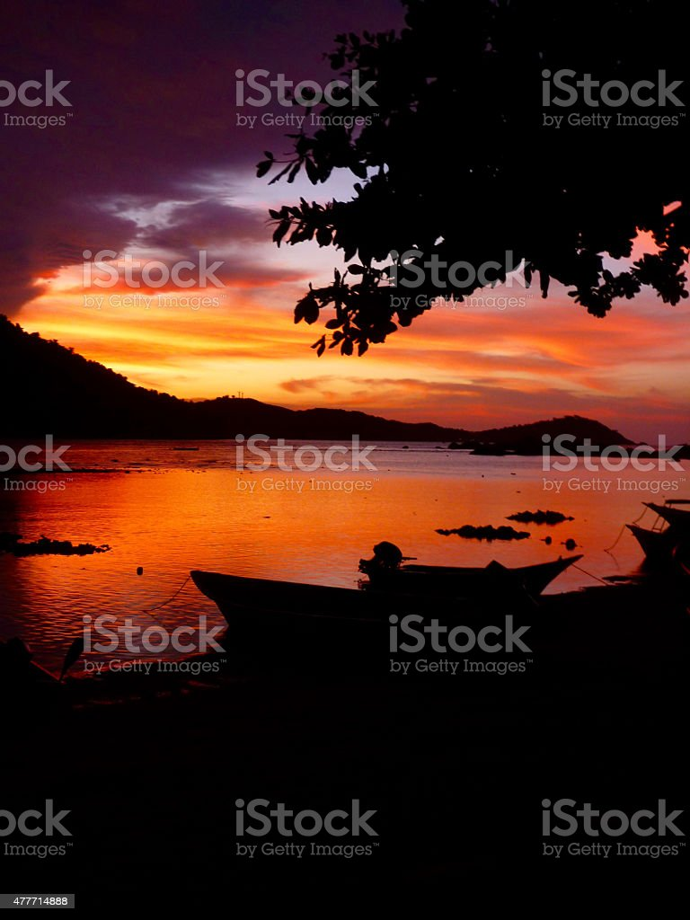 Intense Paradise dramatic red sky sunset over water stock photo