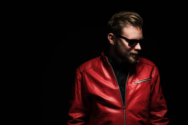Intense portrait of a bearded man Cool man in a red leather jacket with sunglasses standing against a black background. leather jacket stock pictures, royalty-free photos & images