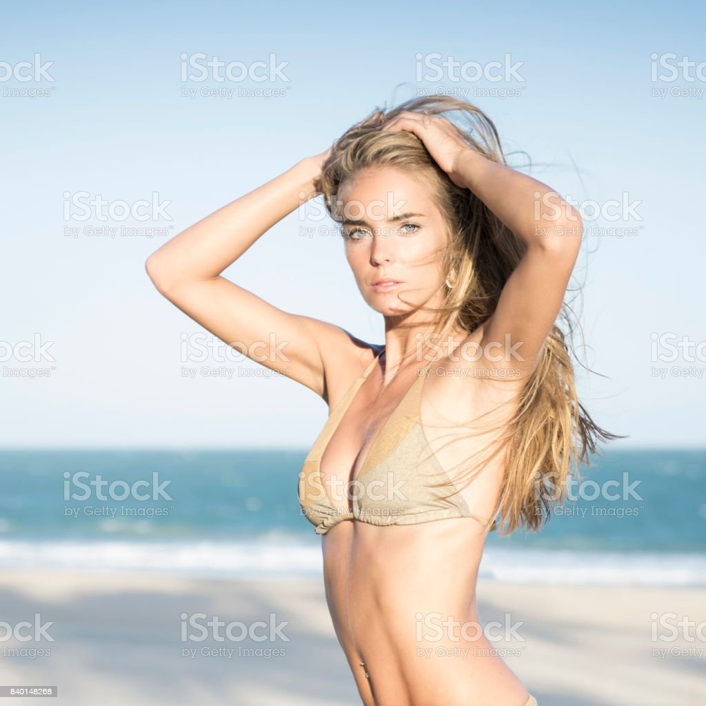 Intense Portrait of a Natural Bikini Beauty watching the sunset at the Beach stock photo