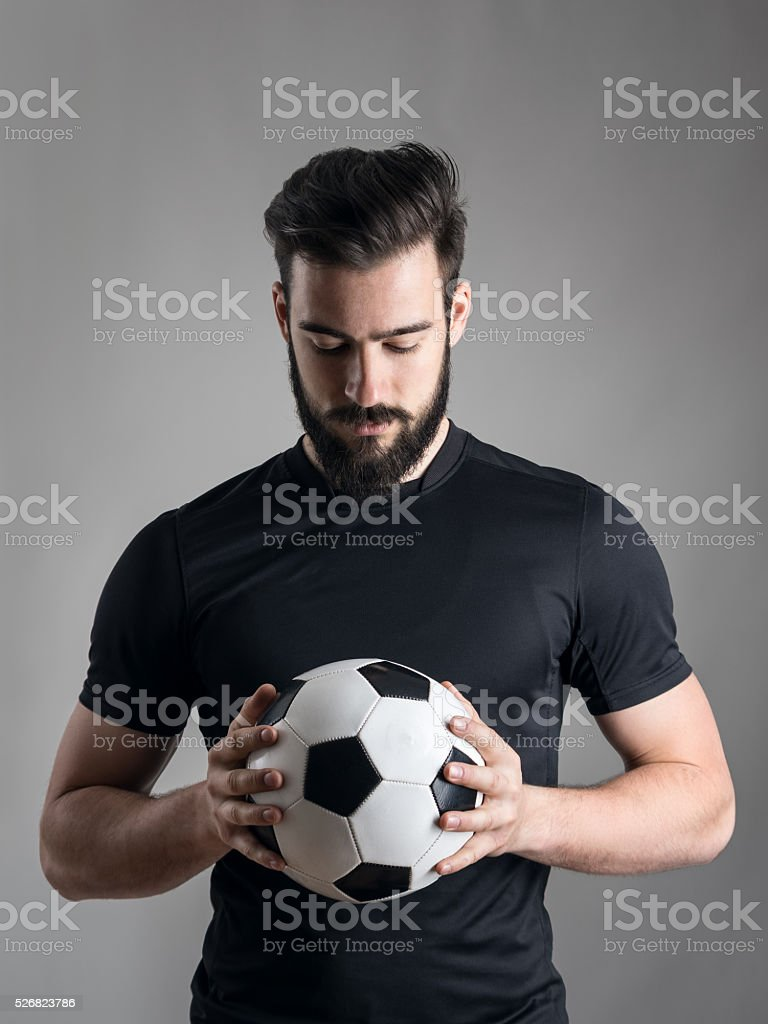 Intense portrait of football player looking at the ball stock photo