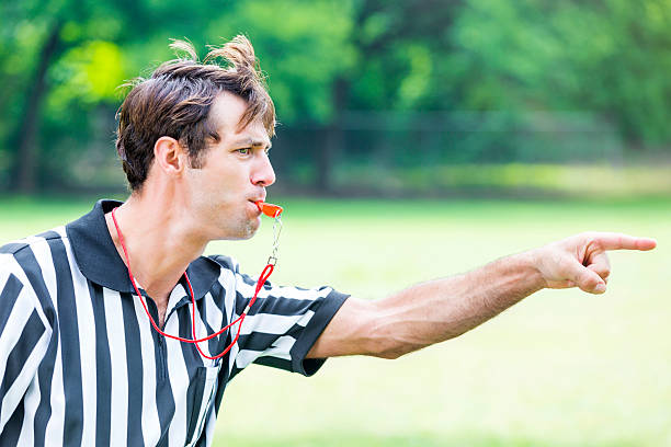 Intense referee calls penalty during sporting event Handsome mid adult Caucasian referee points as he blows his whistle. He is calling a penalty or foul during sporting event. He has brown hair and is wearing a black and white striped referee uniform. He is standing on the playing field. He has an intense expression on his face. referee stock pictures, royalty-free photos & images
