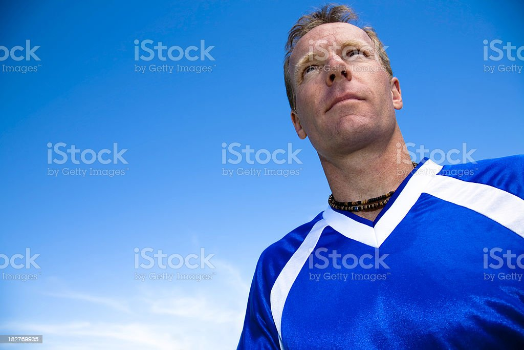 Intense Soccer Player Looking Ahead with Pretty Blue Sky royalty-free stock photo