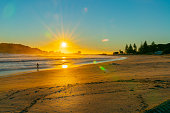 Intense sunrise at Mount Maunganui back lights landscape main beach, Tauranga New Zealand.