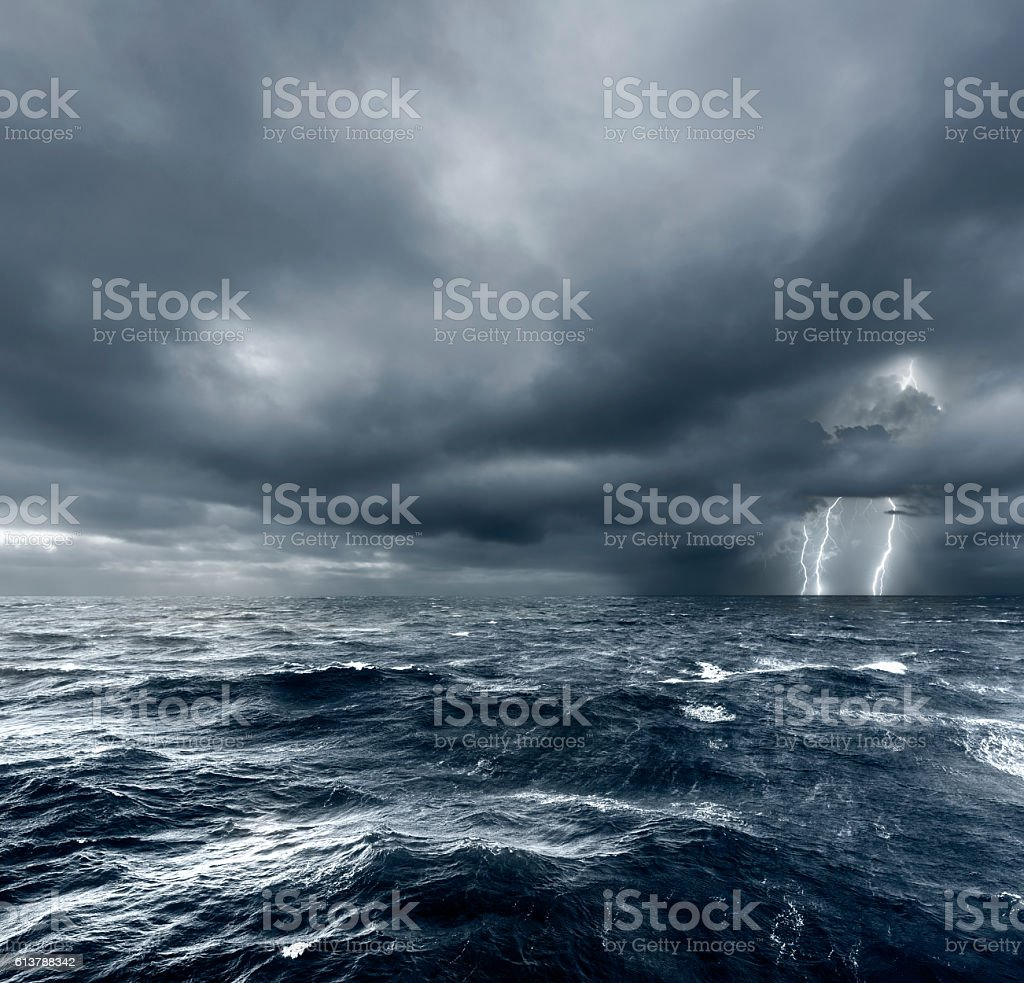 Intense thunderstorm over ocean with lightning. stock photo