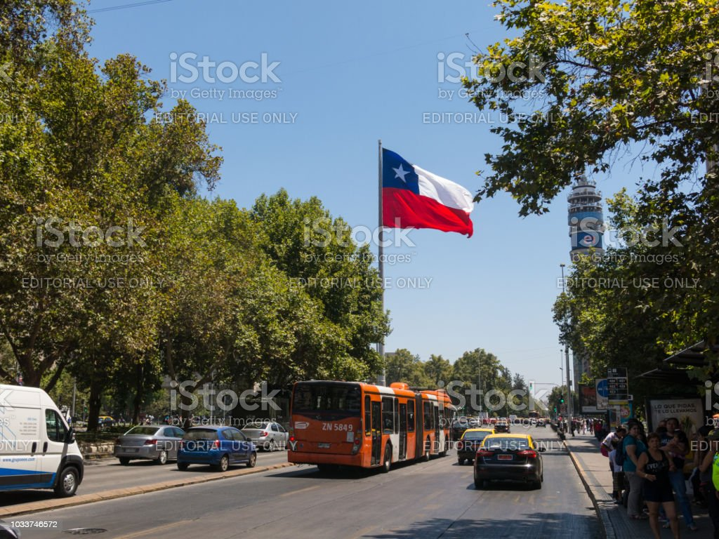 Intense traffic on Avenida La Alameda, the most important street in Santiago de Chile. In the background, the flag of Citizenship Square stock photo