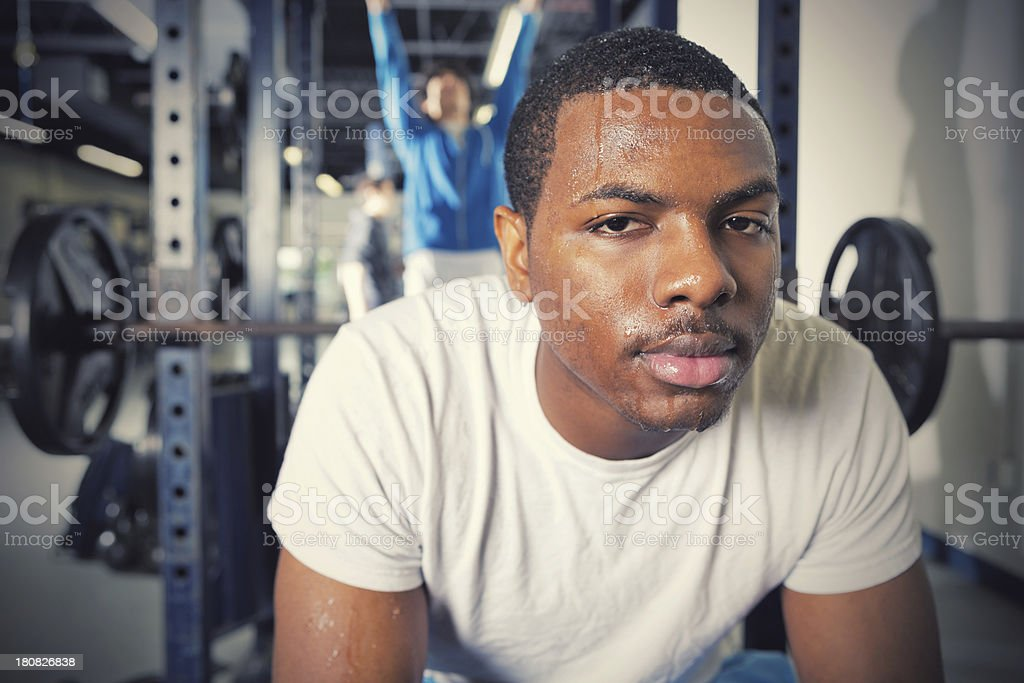 Intense young man resting after lifting weights royalty-free stock photo
