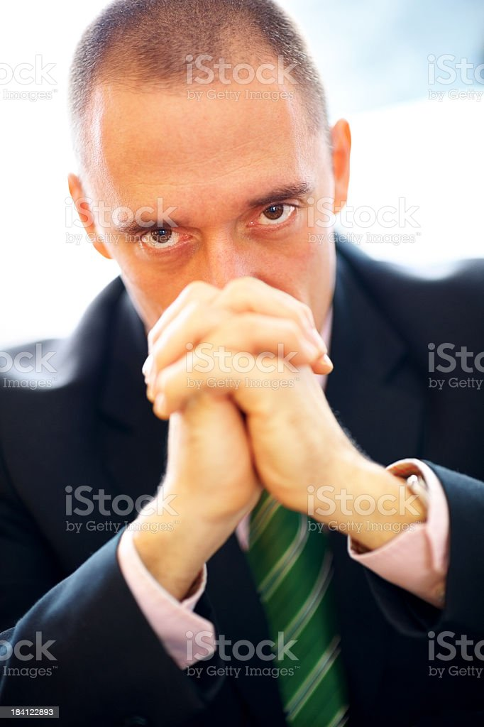 Intensive mature man looking over folded hands royalty-free stock photo