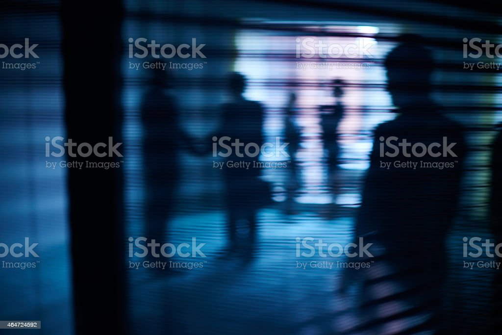 Interacting silhouettes Silhouettes of business people interacting behind window with blinds 2015 Stock Photo