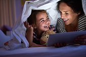 Shot of a mother using a digital tablet with her daughter under a blanket fort