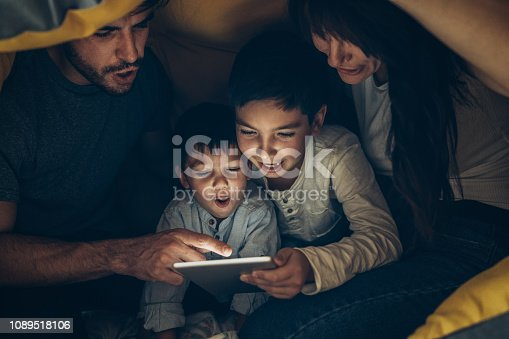 Family reading digital book for children in the bed under blanket