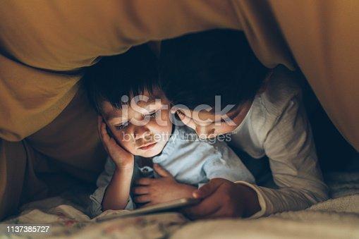 Two brothers using digital tablet under blanket in the dark