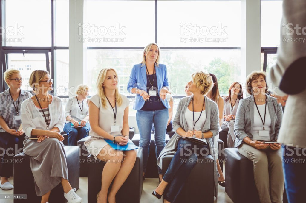 Interactive question and answer session during seminar One of woman asking a question to speaker during conference. Group of business women attending a lecture. Adult Stock Photo