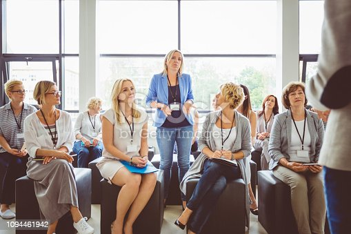 One of woman asking a question to speaker during conference. Group of business women attending a lecture.