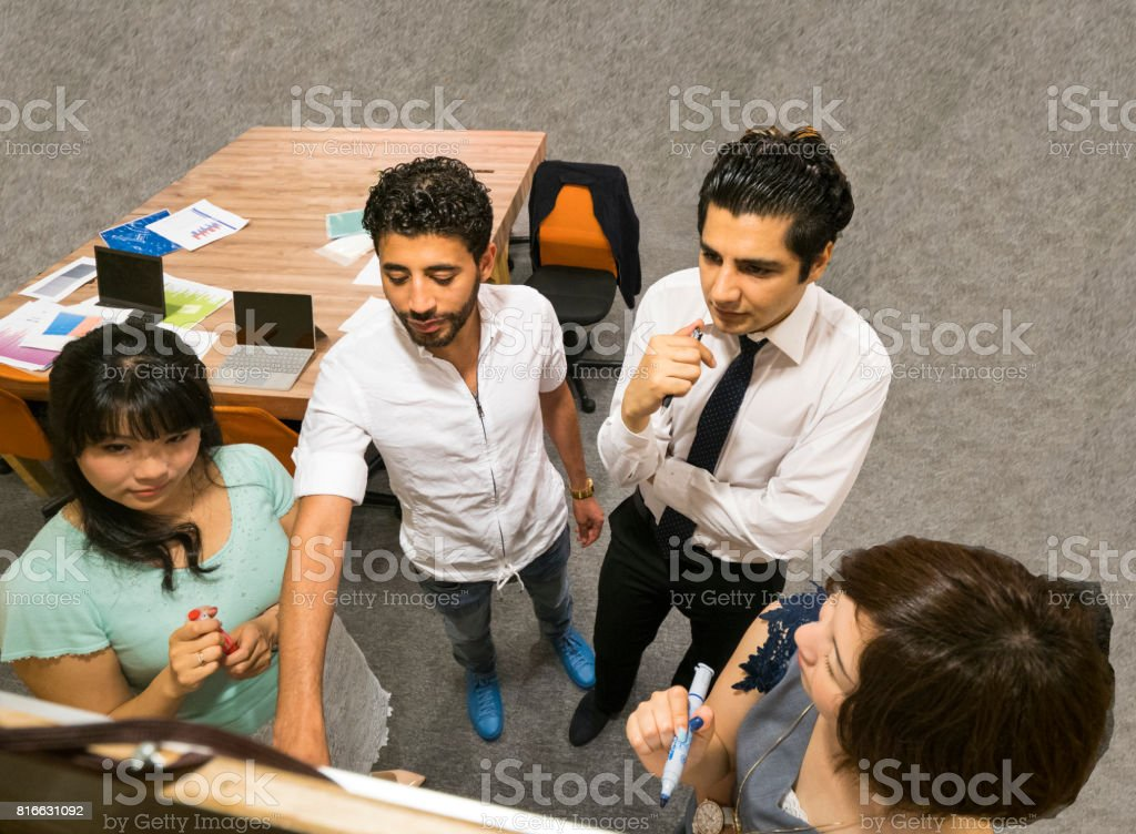 Interantional business people having braingstorming using whiteboard stock photo