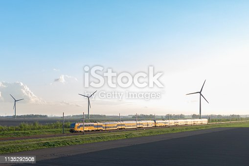 Intercity train of the Dutch Railways driving in springtime landscape with wind turbines in the background