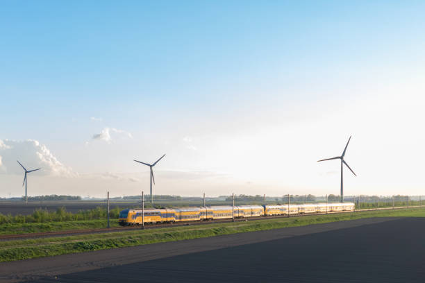 Intercity train of the Dutch Railways driving in springtime landscape with wind turbines stock photo