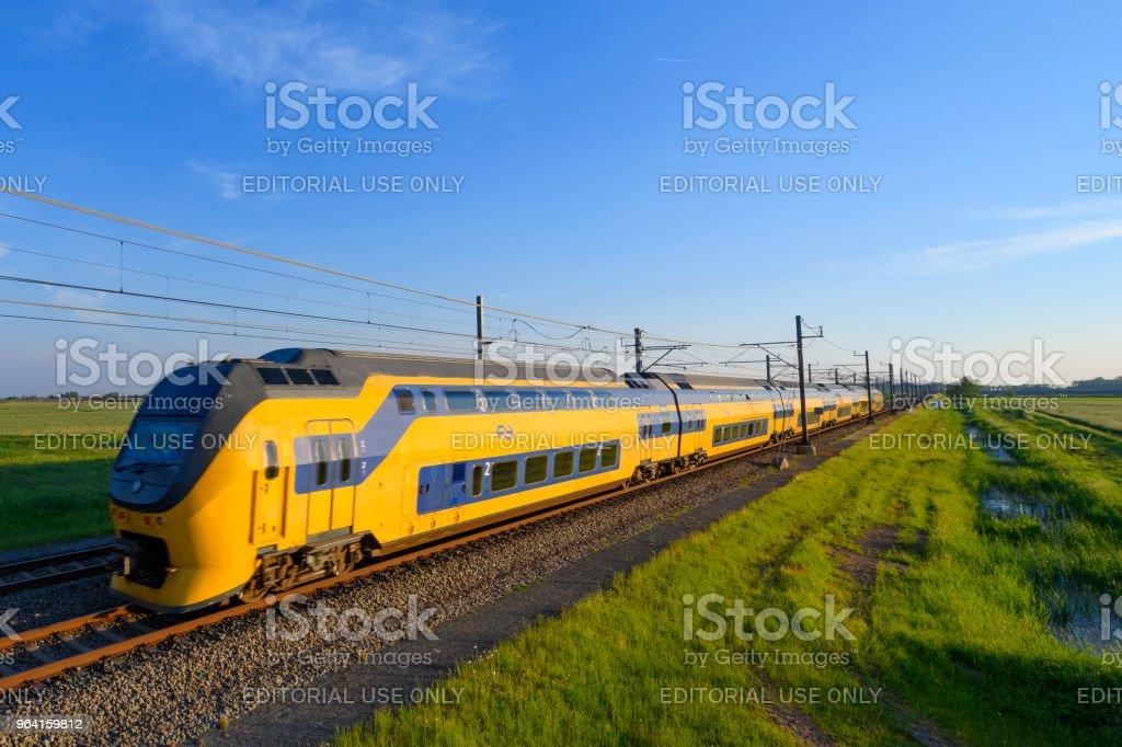 IC-trein van de Nederlandse spoorwegen rijden in lente landschap foto
