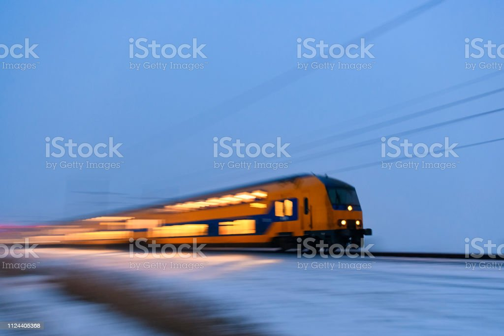 Intercity train of the Nederlandse Spoorwegen (NS) driving through the snow during a cold winter evening - foto stock