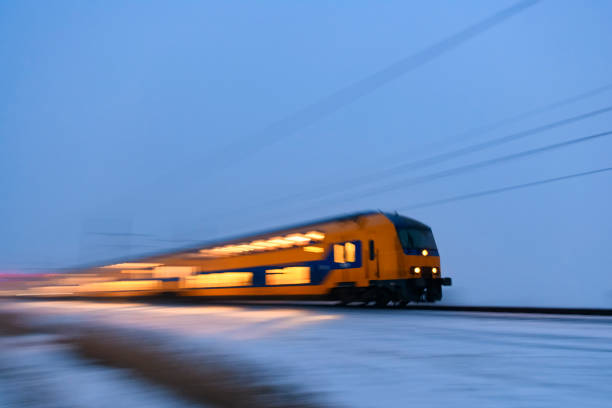 Intercity train of the Nederlandse Spoorwegen (NS) driving through the snow during a cold winter evening stock photo