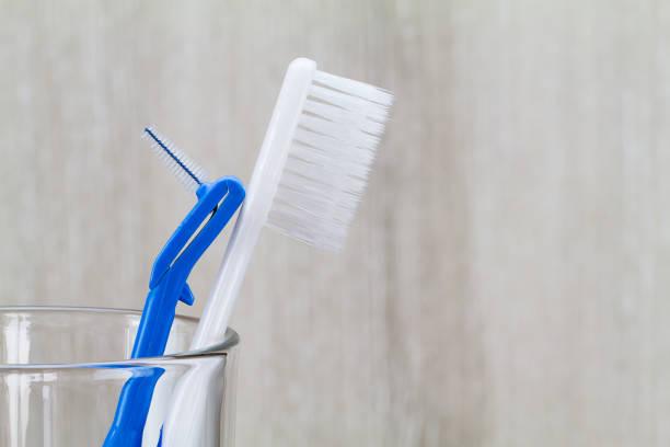 escova interdental e escova de dentes no copo limpo no fundo borrado de madeira, casa de banho - escova interdental - fotografias e filmes do acervo