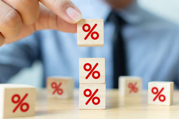 interest rate financial and mortgage rates concept. hand putting wood cube block increasing on top with icon percentage symbol upward direction - interest rate stock photos and pictures