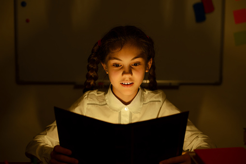 Small girl reading a book in the classroom