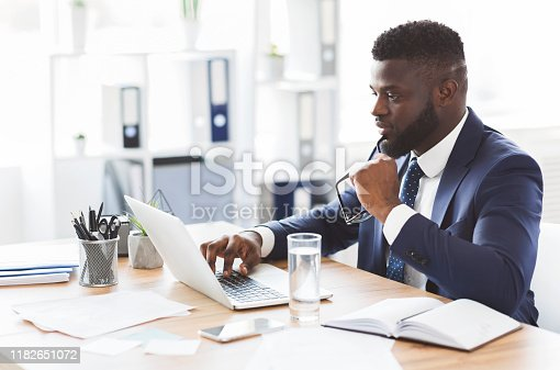 Interested african american businessman checking new website for entrepreneurs, office interior, copy space
