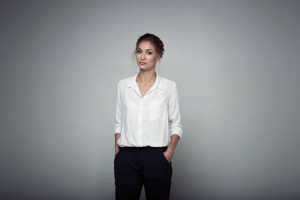 Interested businesswoman with trendy makeup posing on gray background in studio. Indoor photo of serious young lady in white blouses classic black pants standing in confident pose. stock photo