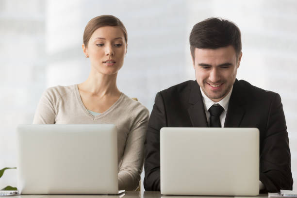 Interested curious businesswoman looking at businessman laptop screen, corporate espionage stock photo