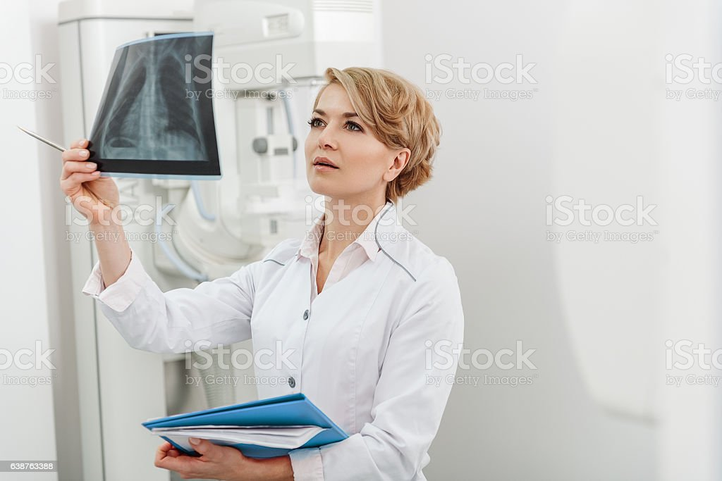 Interested female doctor holding radiograph stock photo