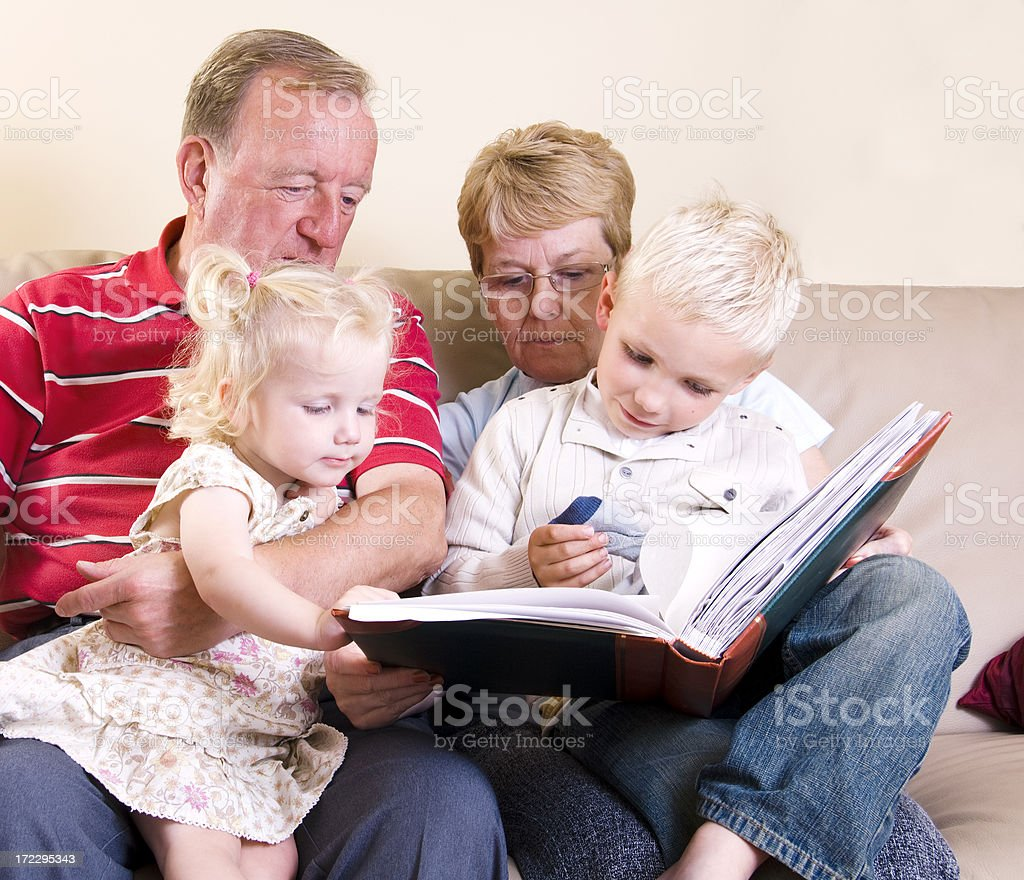 interested grandchildren learning on grandaparents lap royalty-free stock photo