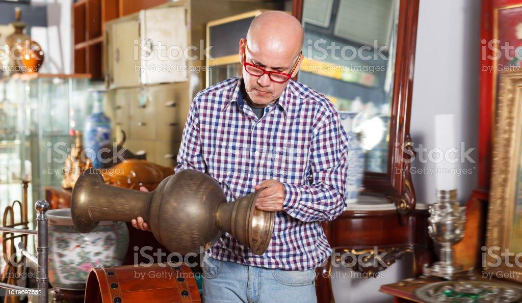 Interested happy man measuring vintage amphora stock photo