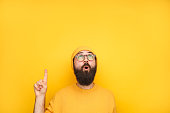 istock Interested hipster pointing up on yellow 945088482