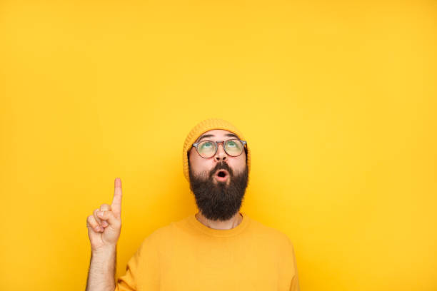 Interested hipster pointing up on yellow stock photo